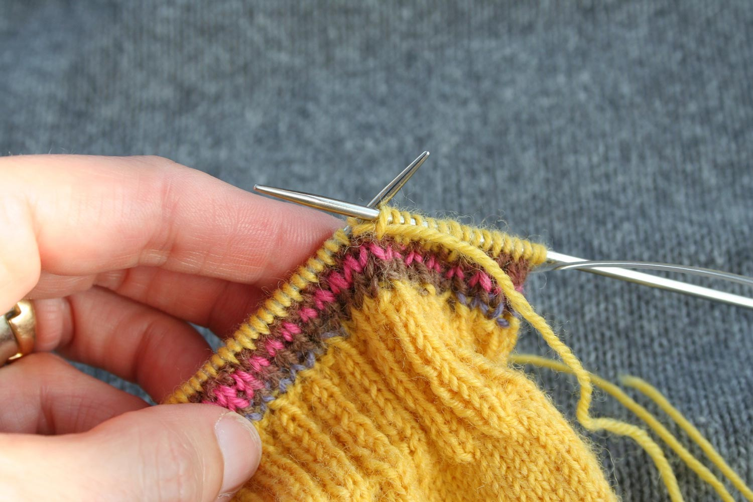 Knitting in the round with working yarn running through the first stitch on the left needle and then the last stitch on the right needle.