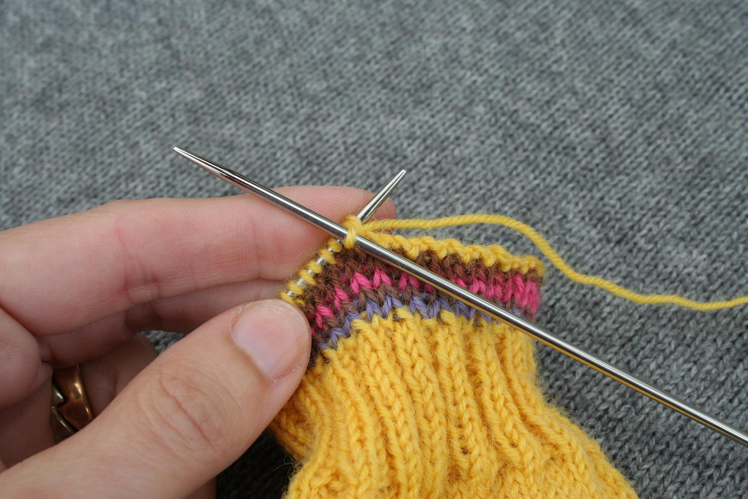 Bind off being worked on a sock cuff with right needle performing a knit two together (k2tog).