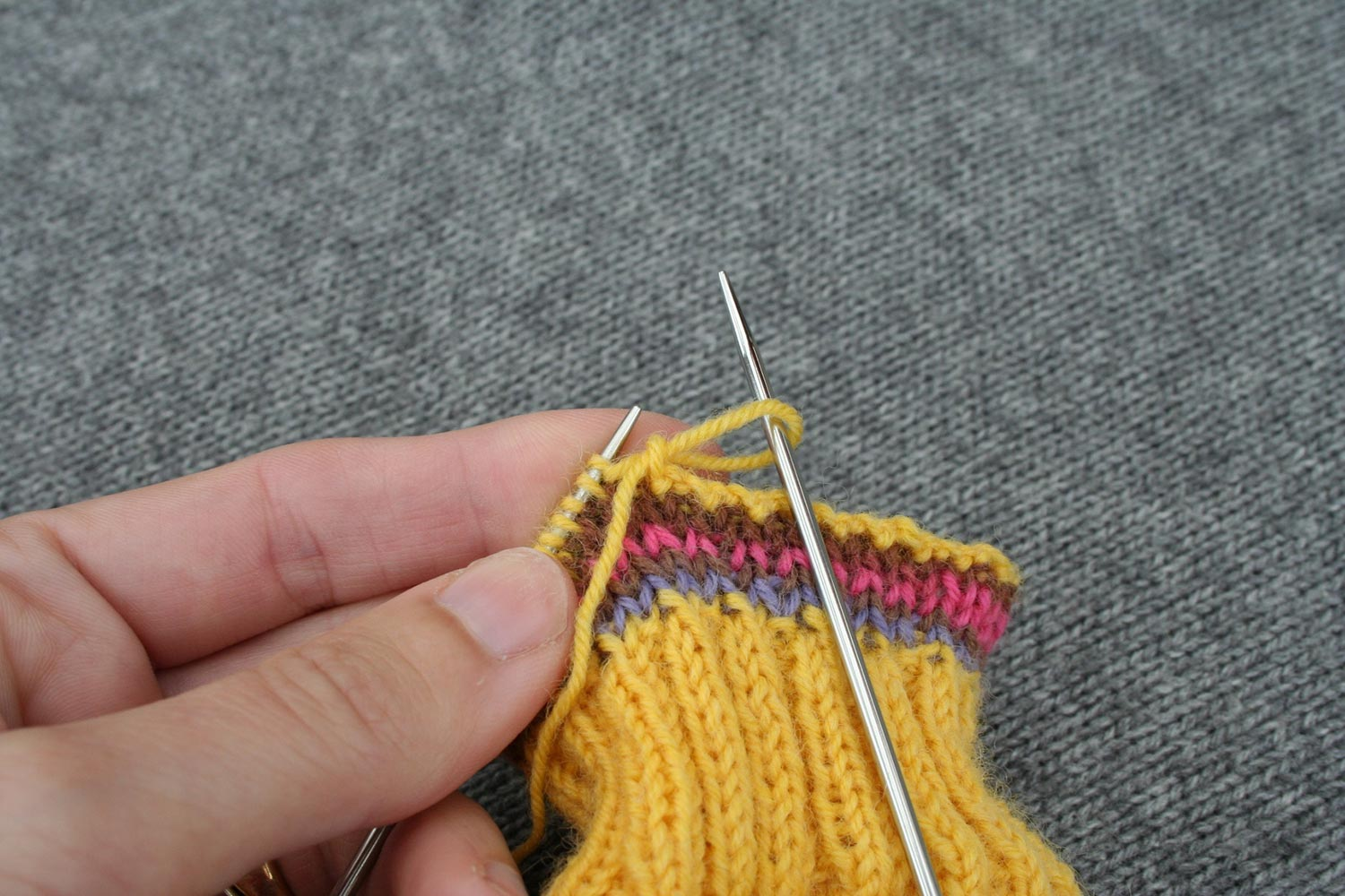 Needle pulling on the only stitch on right needle to enlarge it and pull the tail through.