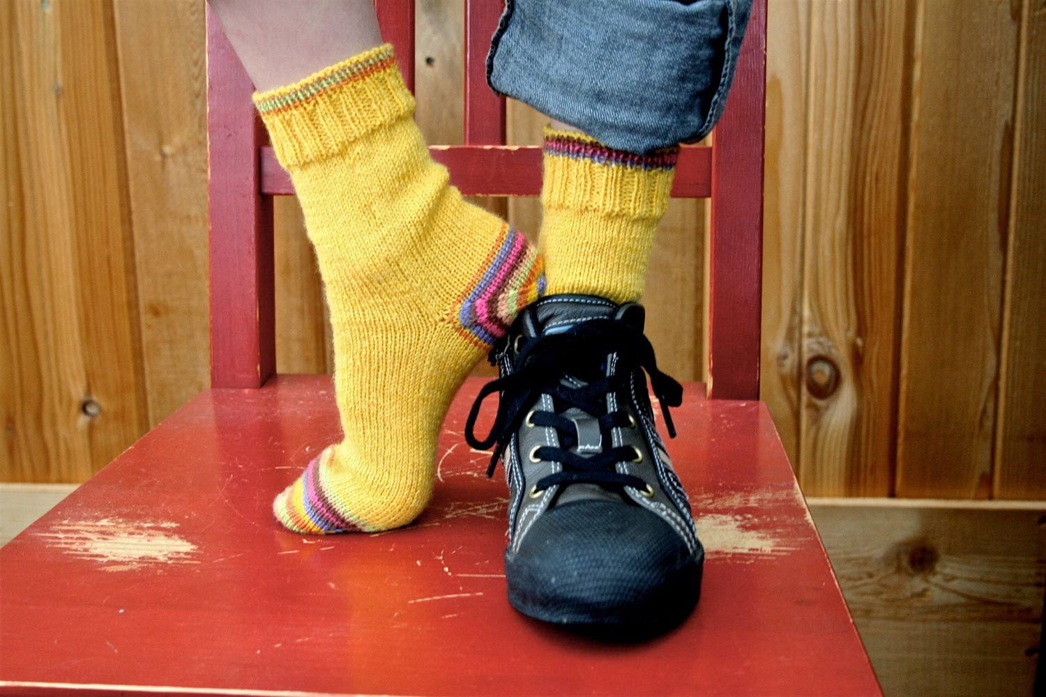Feet standing on a chair wearing yellow hand knit socks worked toe up with a stripey heal and toe, modelled with one shoe on and one shoe off.