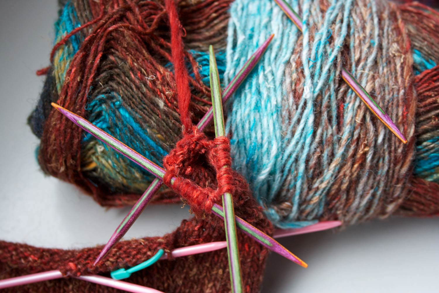Stitches on three double pointed needles and finger partially knit, leaning agains a ball of yarn.