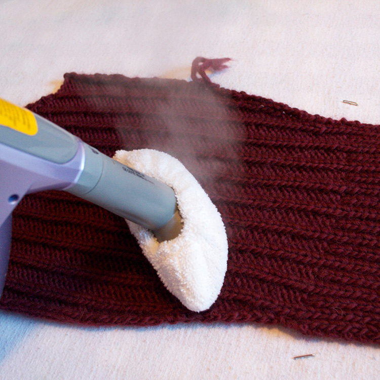 Steam billowing out of a hand held steamer held over a hand knit sleeve piece.