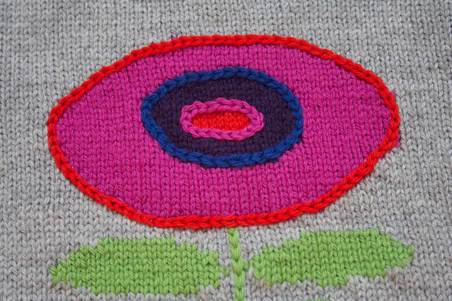 A knitted flower formed with concentric circles of colour worked in the intarsia technique, bordered with contrasting colour chain stitch embellishment.