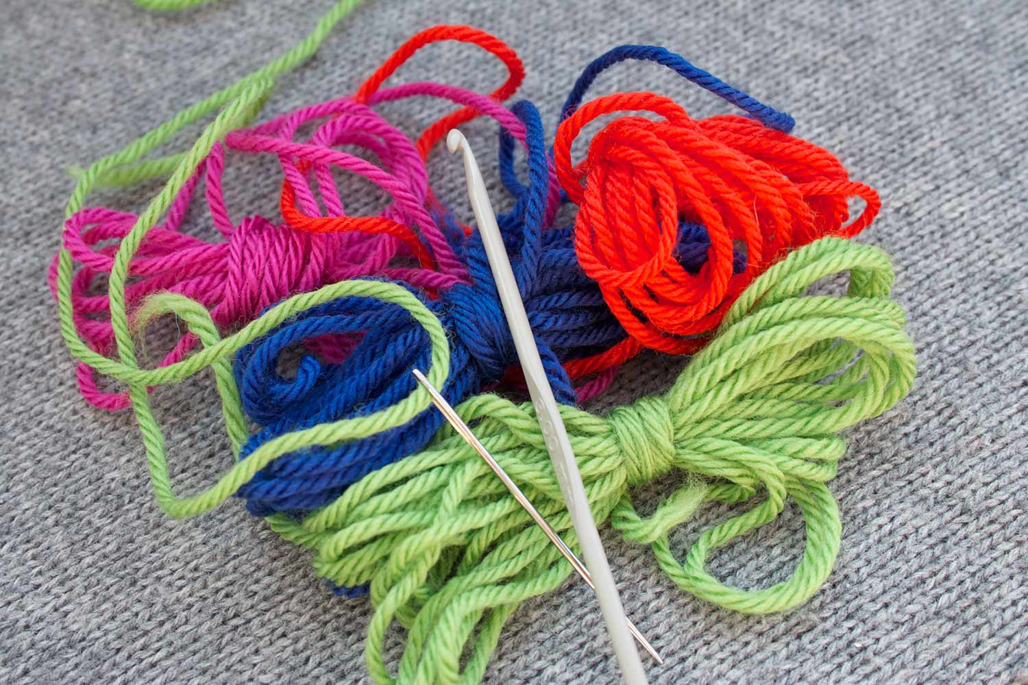 Several butterflies of yarn in bright colours with a crochet hook and threaded tapestry needle resting on top.