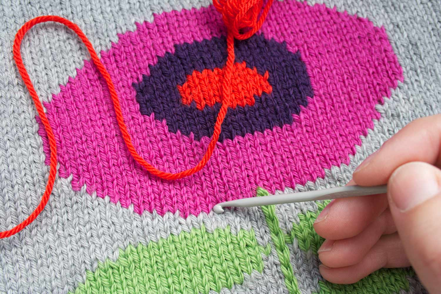 Crochet hook held in right hand and pointing to a location on the outside of the flower motif where the hook will be inserted through the fabric.