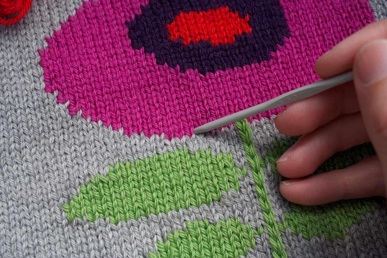 Crochet hook inserted through knitting fabric along outside edge of an intarsia flower motif.
