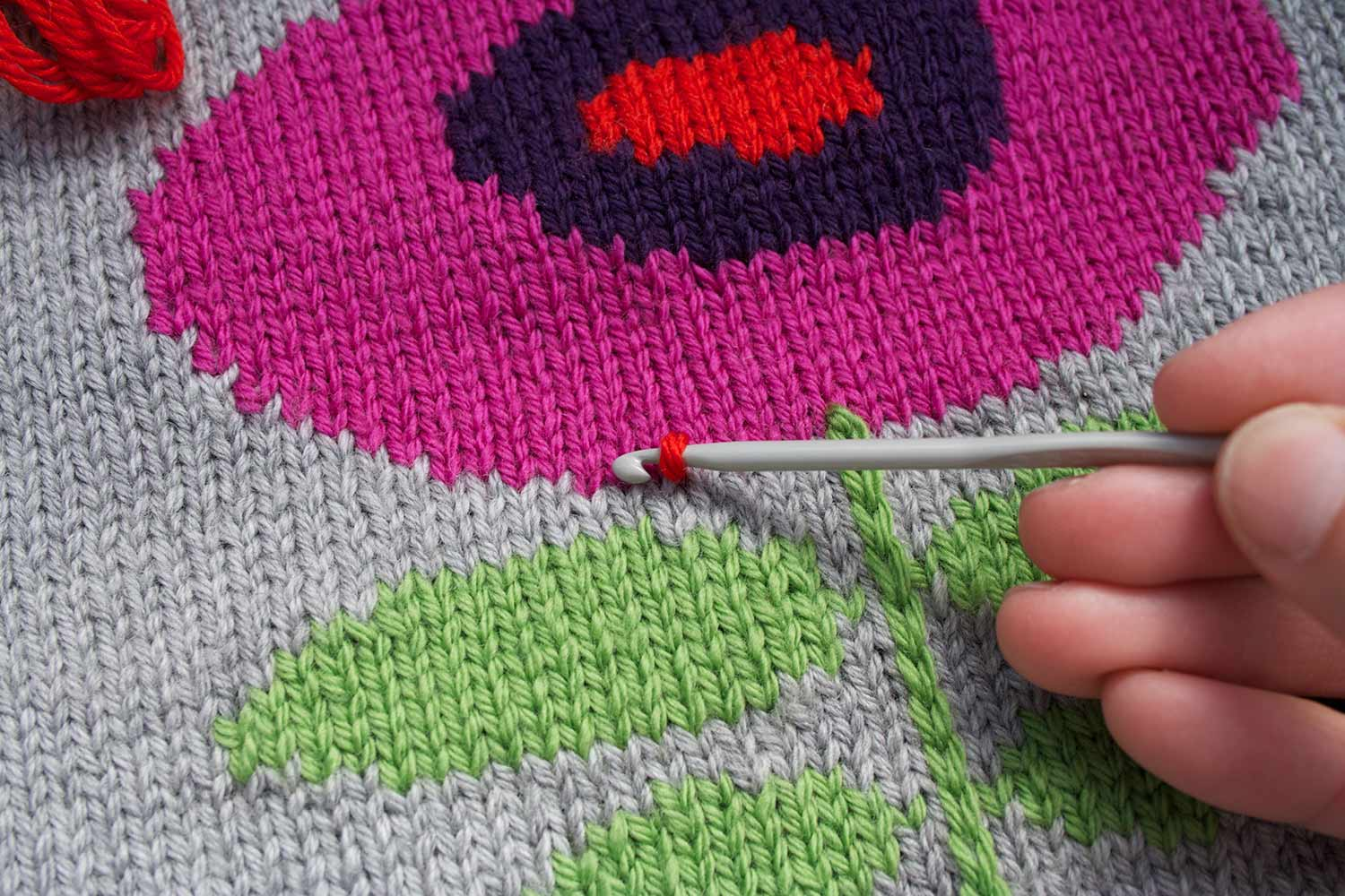 Crochet hook with a loop of yarn round it forming a stitch that has been drawn through knitted fabric at the edge of an intarsia flower motif.