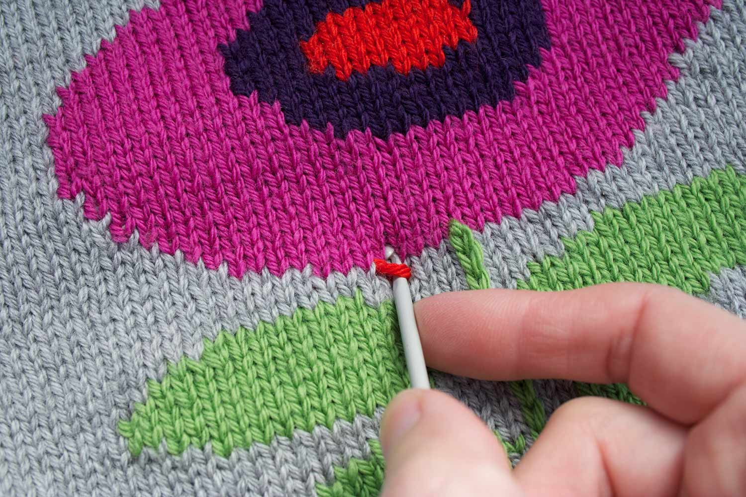 Crochet hook with a stitch on it being inserted through knitted fabric to the right of where the previous stitch was created.