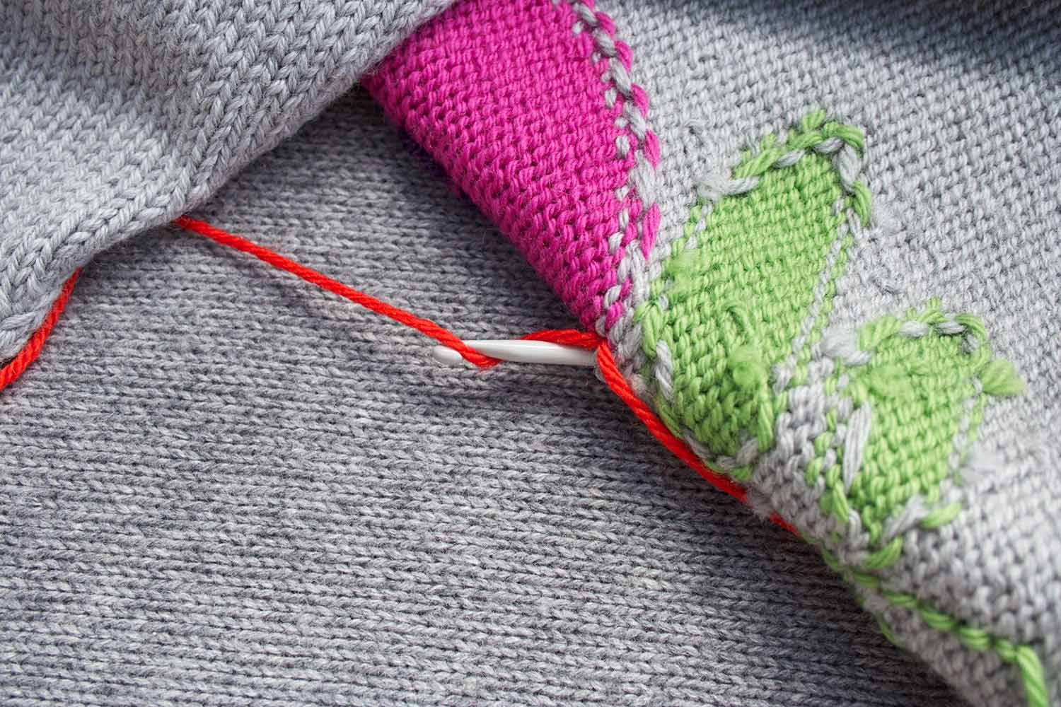 View of back side of knitted fabric with head crochet hook coming through fabric and yarn wrapped around the hook.