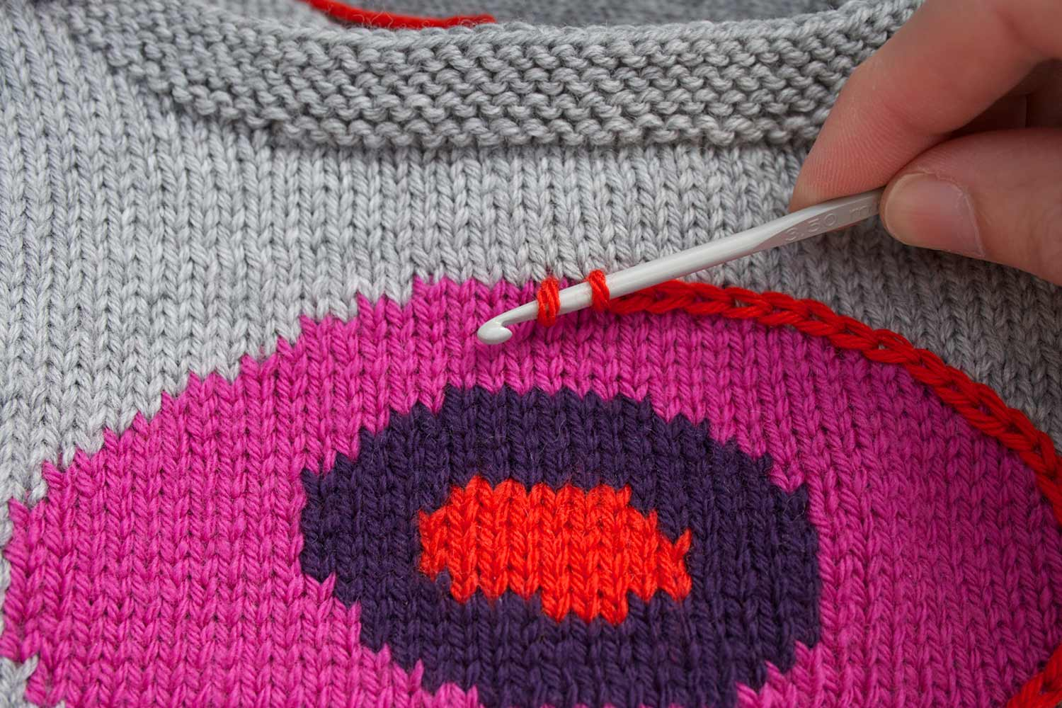 Several chain stitches created with a crochet hook bordering a circular motif worked in intarsia; crochet hook has two stitches on it.