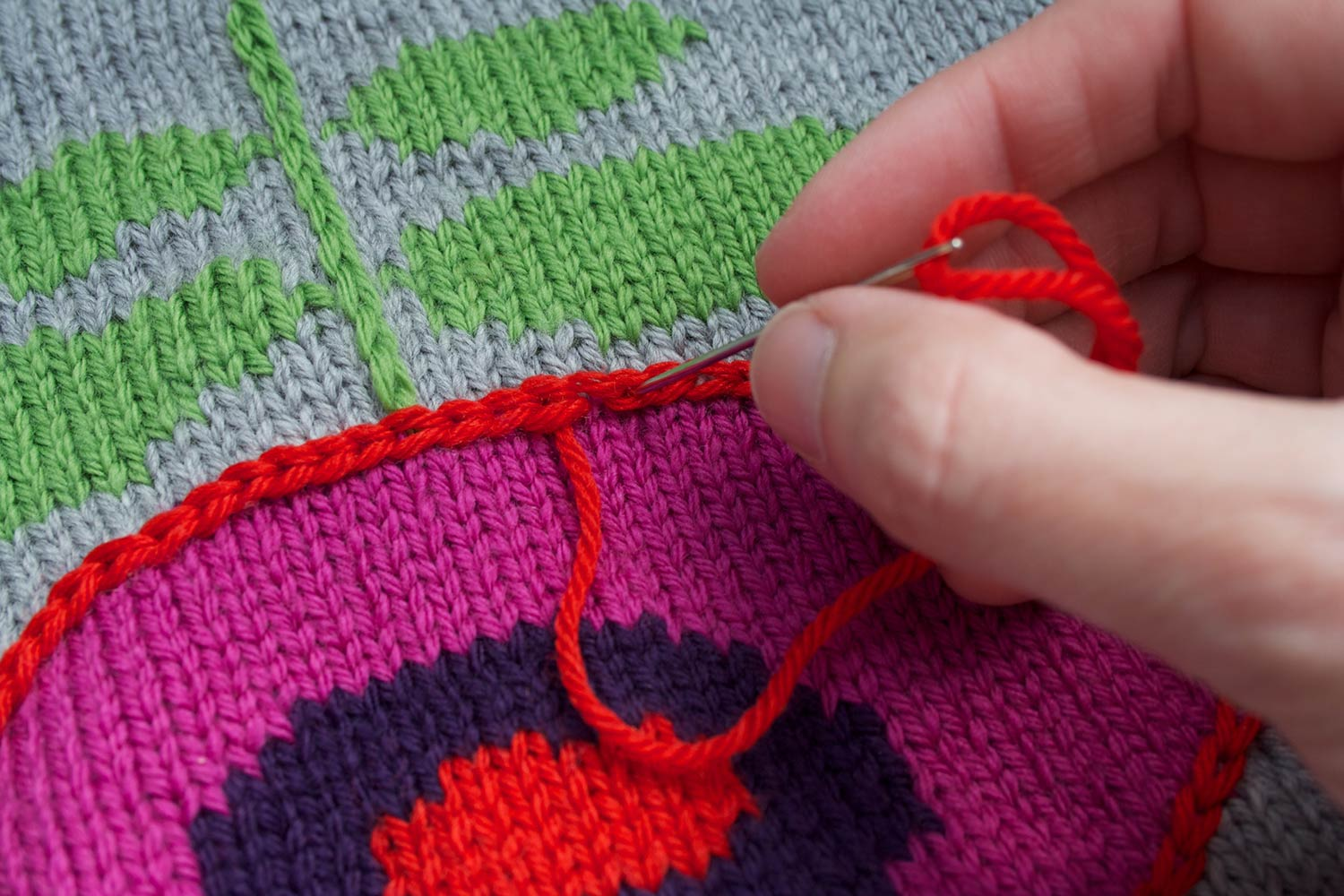 Fingers inserting tapestry needle into centre of last chain stitch worked, in order to complete the final stitched chain stitch.