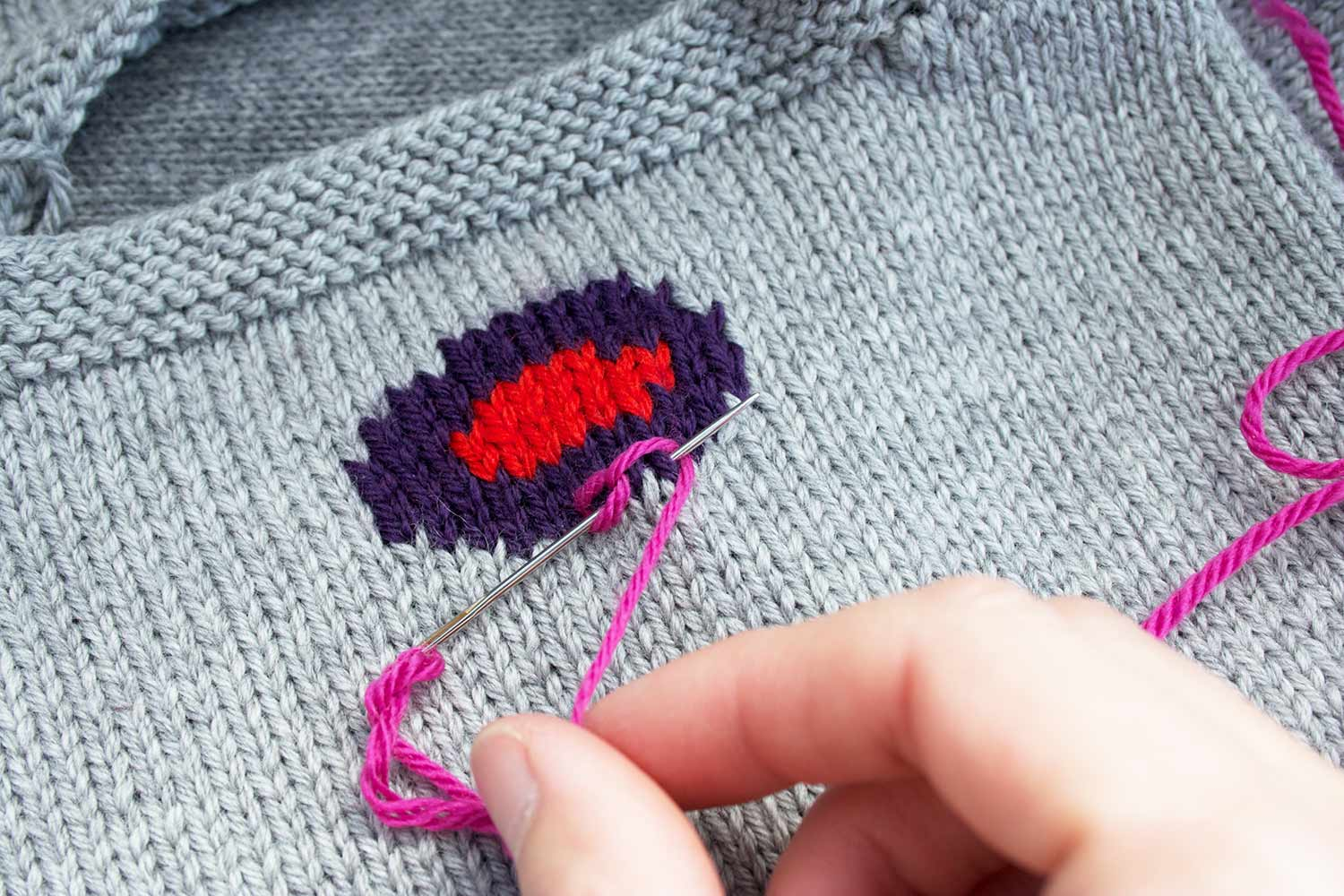 Fingers holding yarn looped under tip of needle while needle is still inserted in knitted fabric.