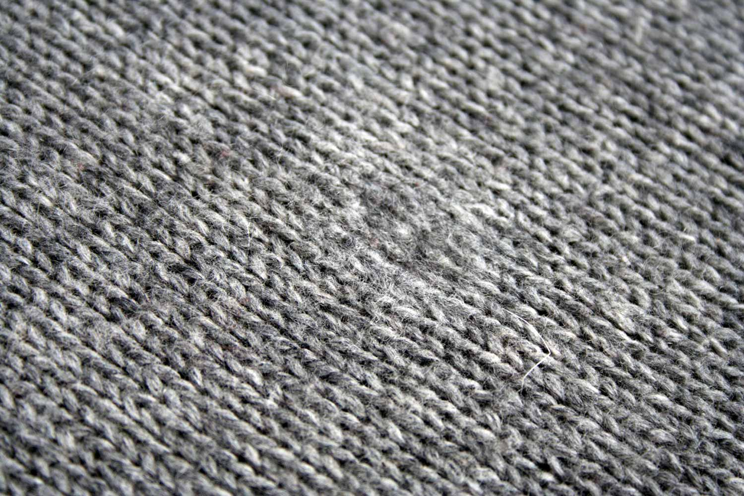 Grey stocking stitch knitted fabric with an area in centre where the stitches are less distinct.