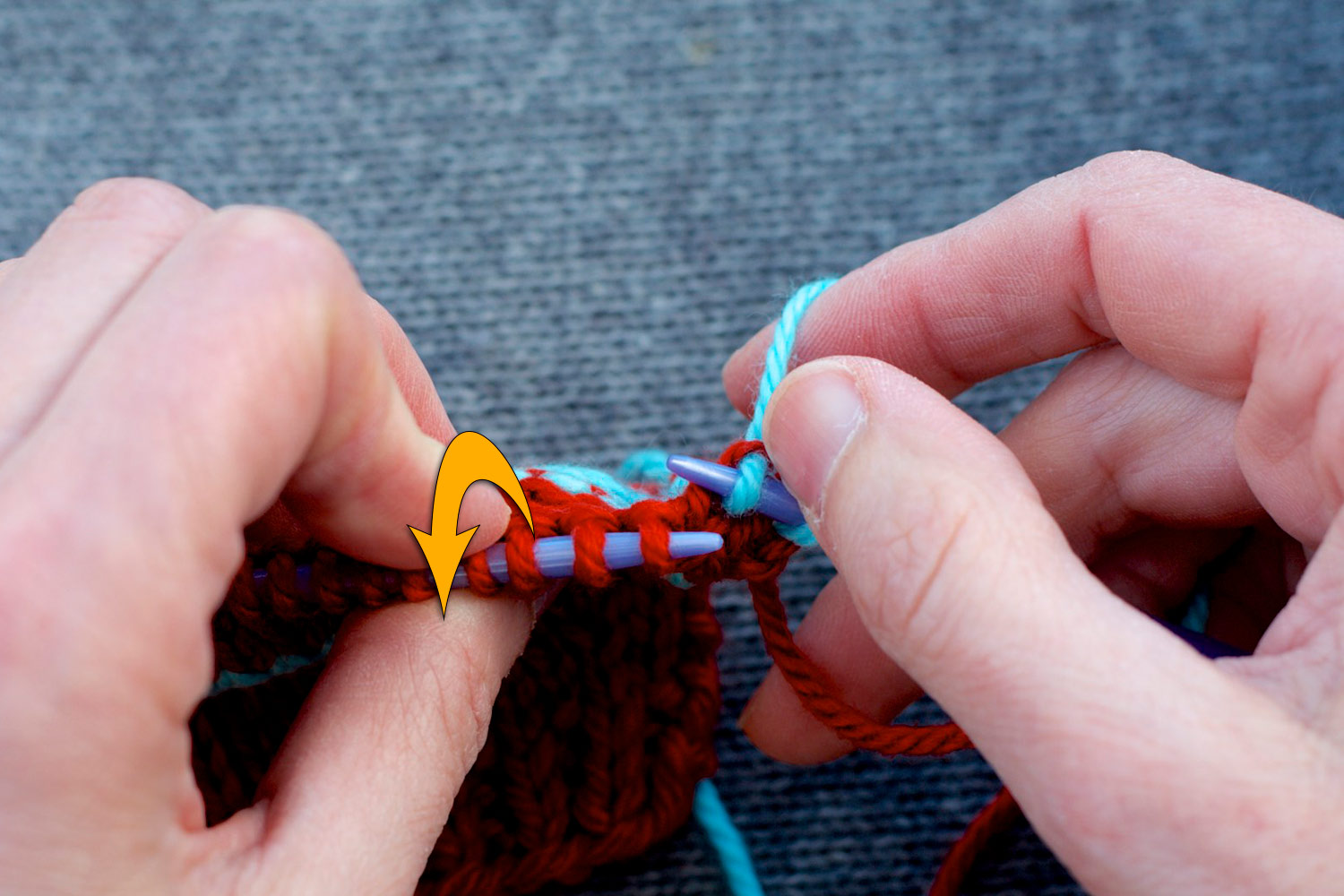 Stitches on the knitting needles with left needle tilted forwards (as indicated by large yellow arrow) to show purls bumps on wrong side.
