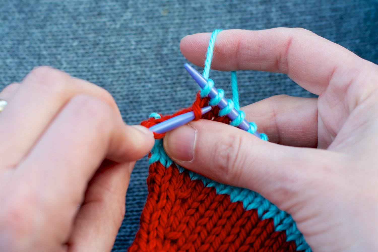 Tip of left knitting needle inserted into left leg of stitch, two rows below last stitch on right needle.