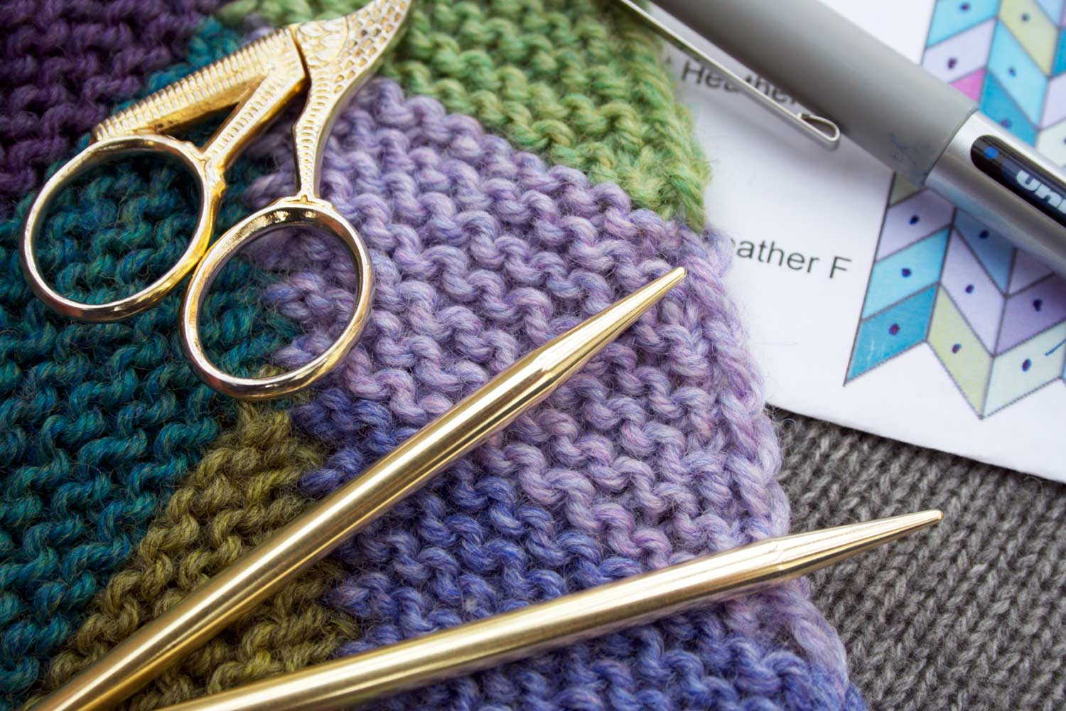 Garter stitch parallelograms forming chevrons with a pair of knitting needles, scissors, and pen resting on top.