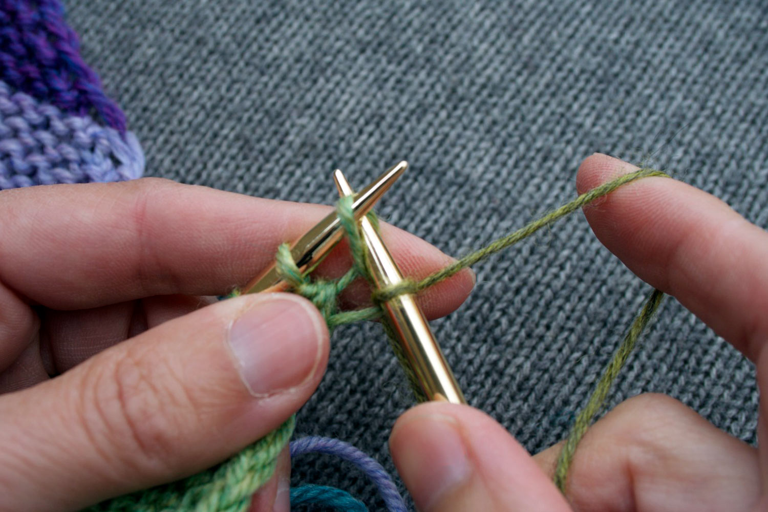 Right needle has already knit into the front of the next stitch on left needle and is now knitting into the back of the same stitch.
