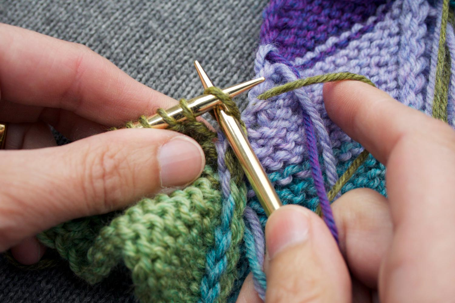 With wrong side facing, right needle inserted in first stitch knitwise, preparing to slip it off.