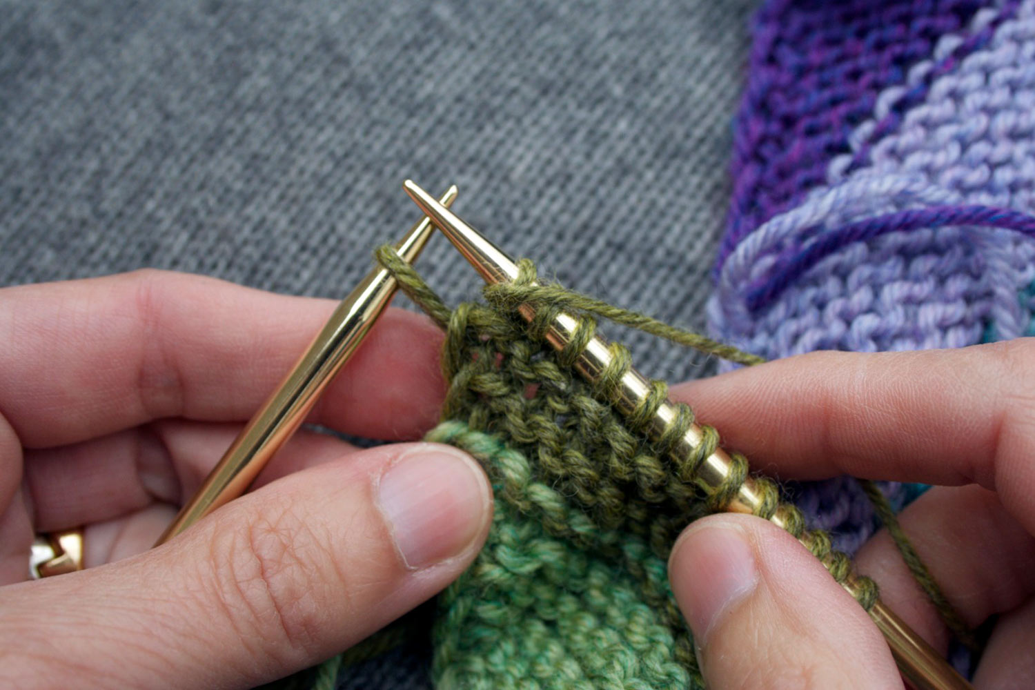 End of wrong side row almost complete, showing yarn in front between needles and one stitch left on left needle.