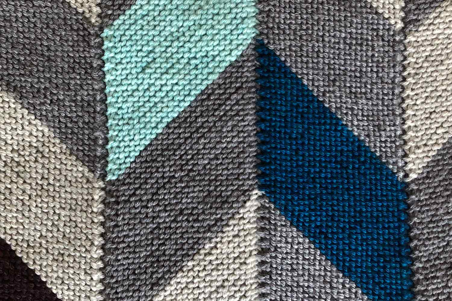 Right side of garter stitch modular knitting with colourful parallelogram shapes joined to created chevrons.
