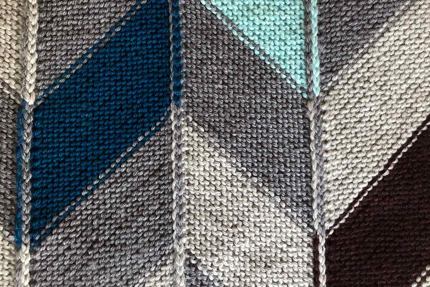 Wrong side of garter stitch modular knitting with colourful parallelogram shapes joined to created chevrons and showing modular seams.
