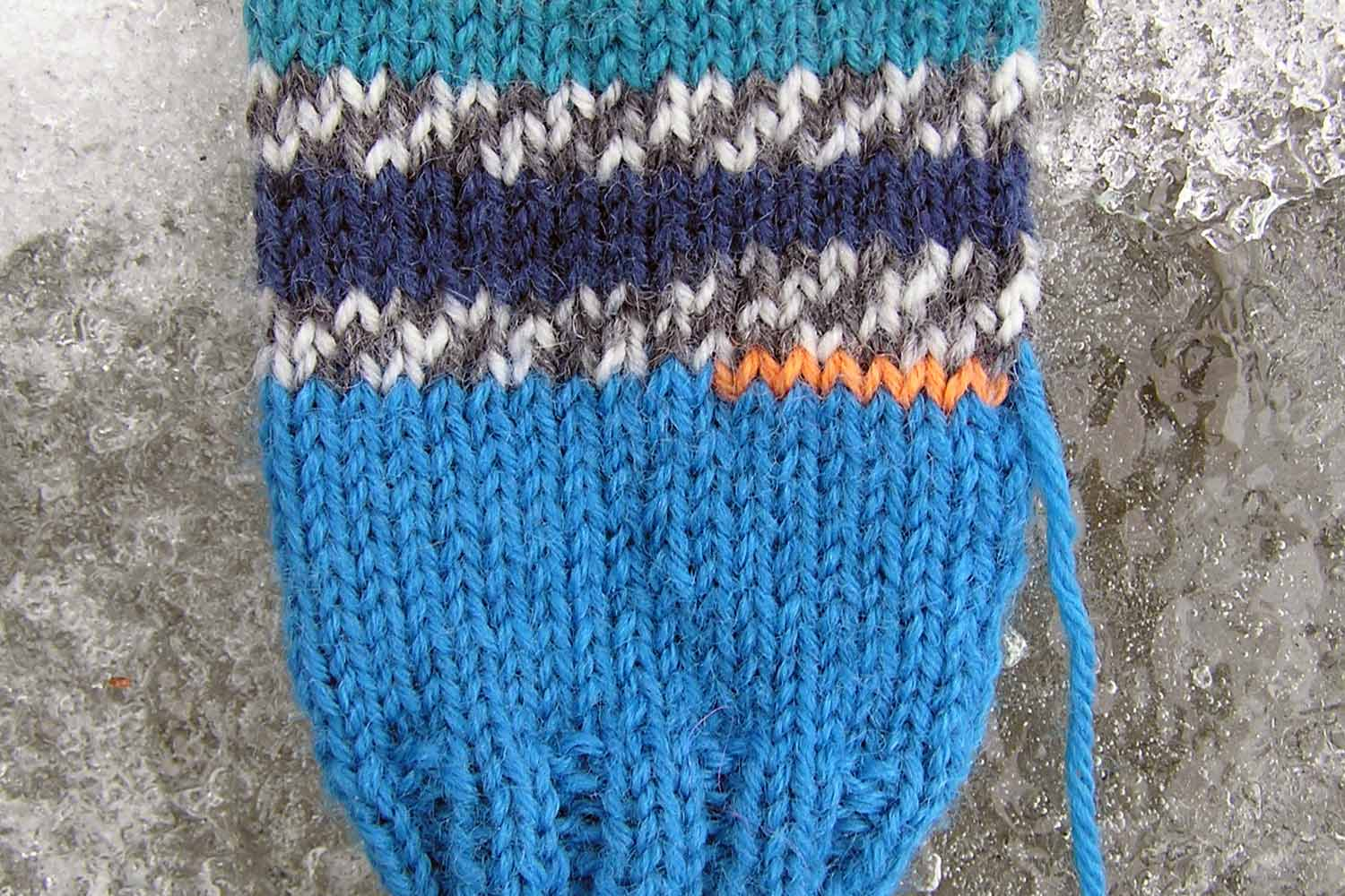 Closeup of the palm section of a mitten with seven orange waste yarn stitches reserving a spot for the thumb.