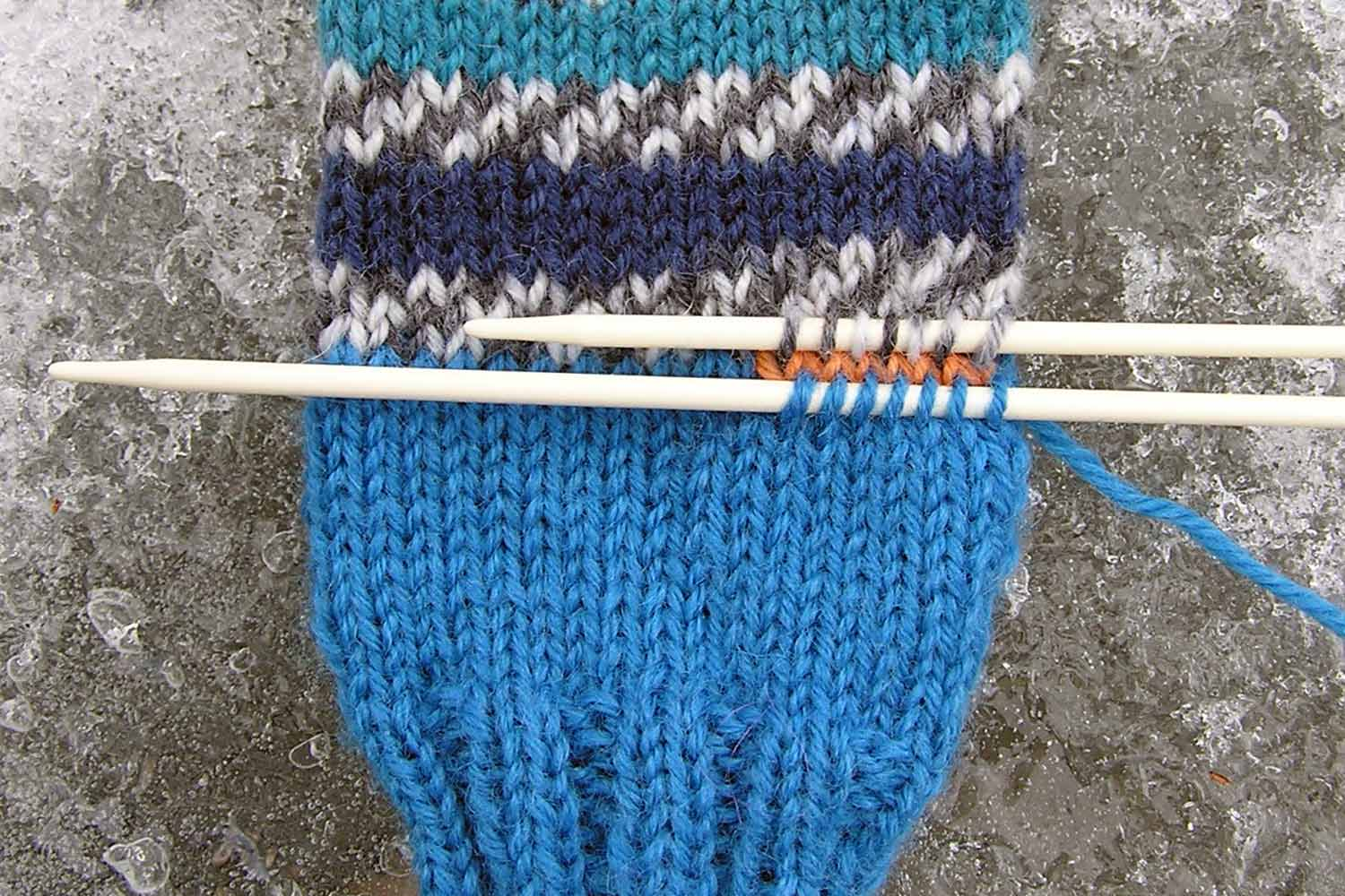 A small double pointed needle is inserted through seven stitches in the row immediately below the waste yarn stitches and another needle holds seven stitches in row immediately above waste yarn stitches.