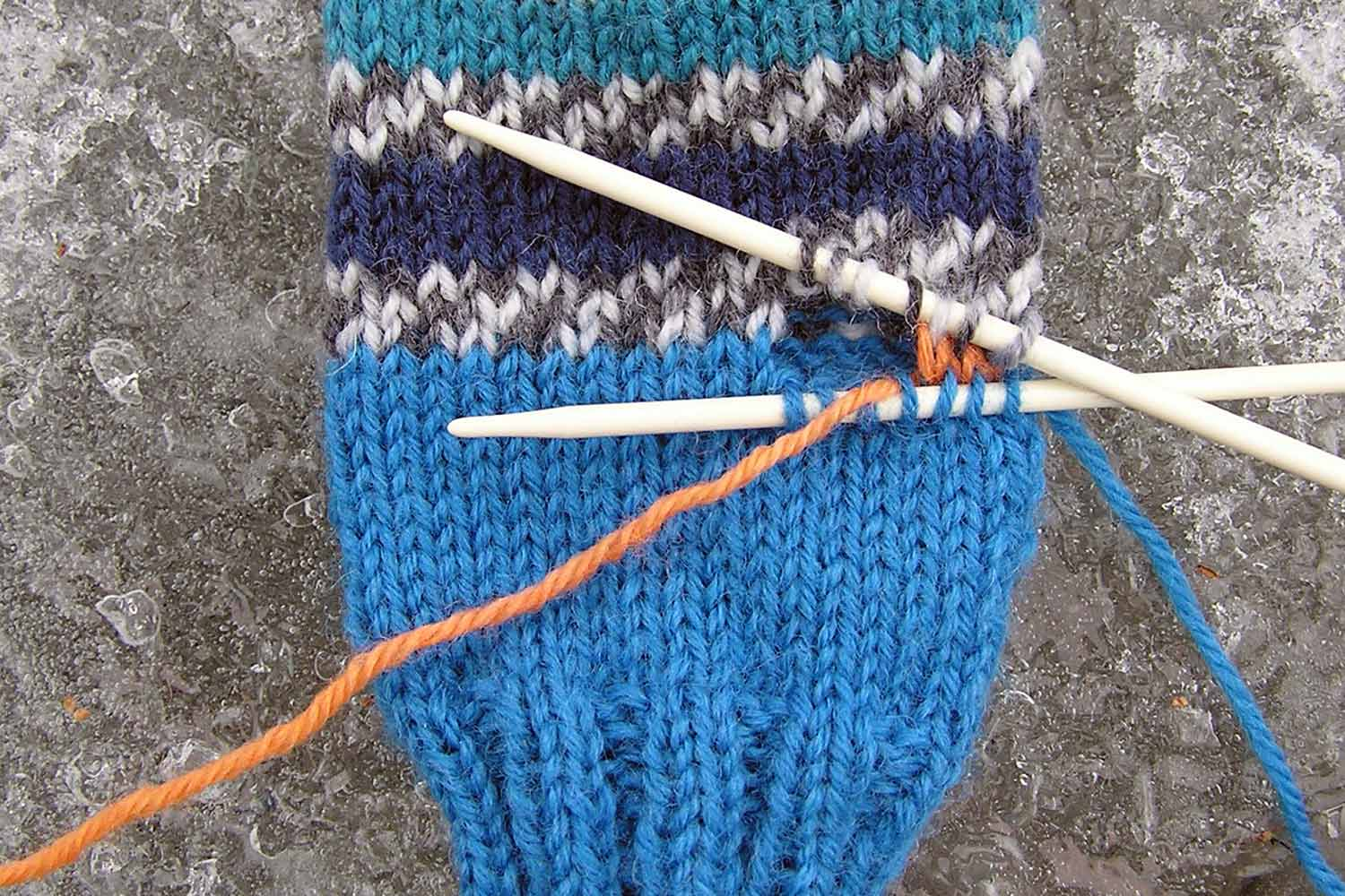 Half of orange waste yarn stitches have been unpicked with two separate needles holding stitches above and below waste yarn.