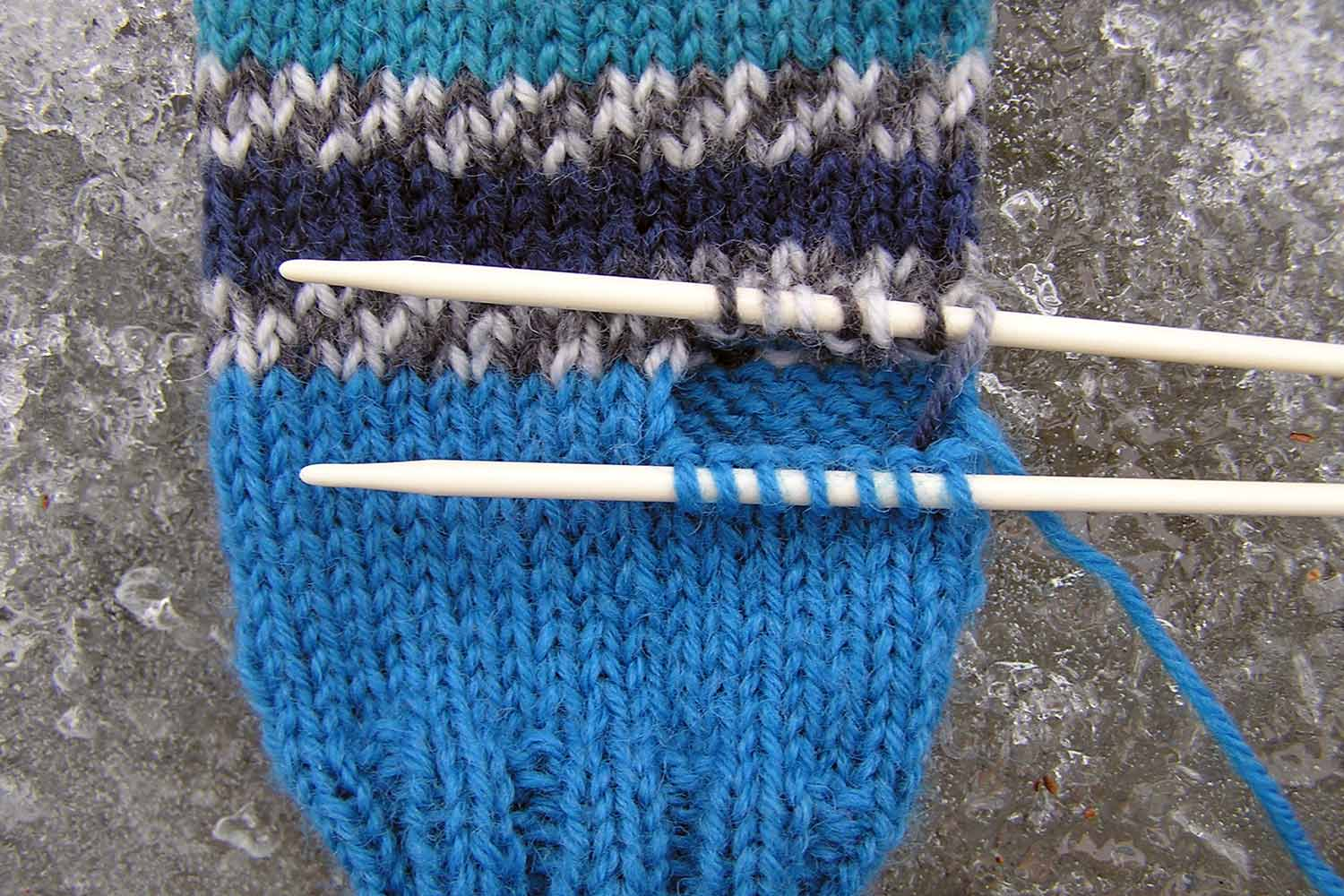 A hole for the thumb has been created in the mitten with live stitches safely preserved on two separate needles.