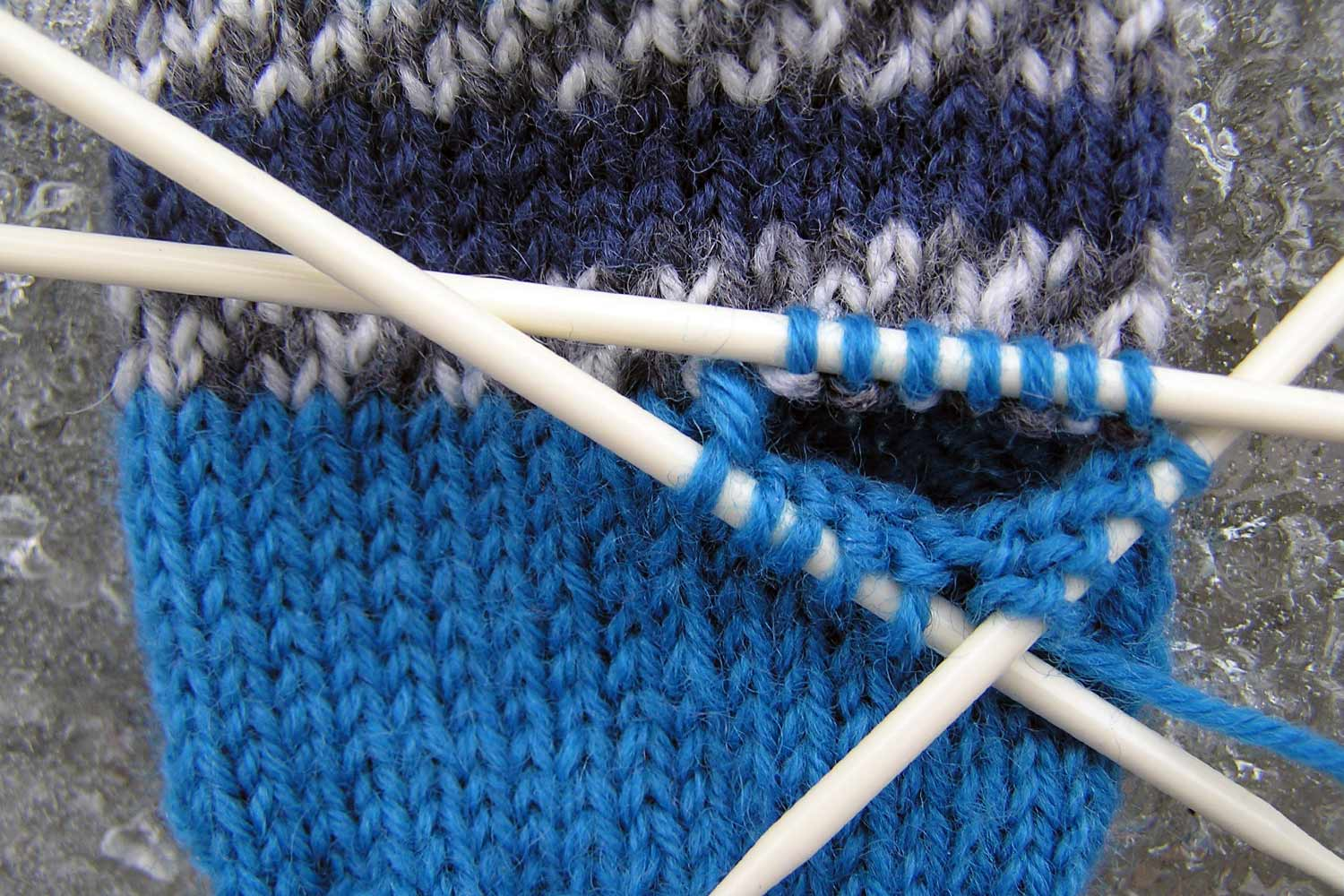 Three double pointed needles with thumb stitches on them frame the hole in the mitten for the thumb.