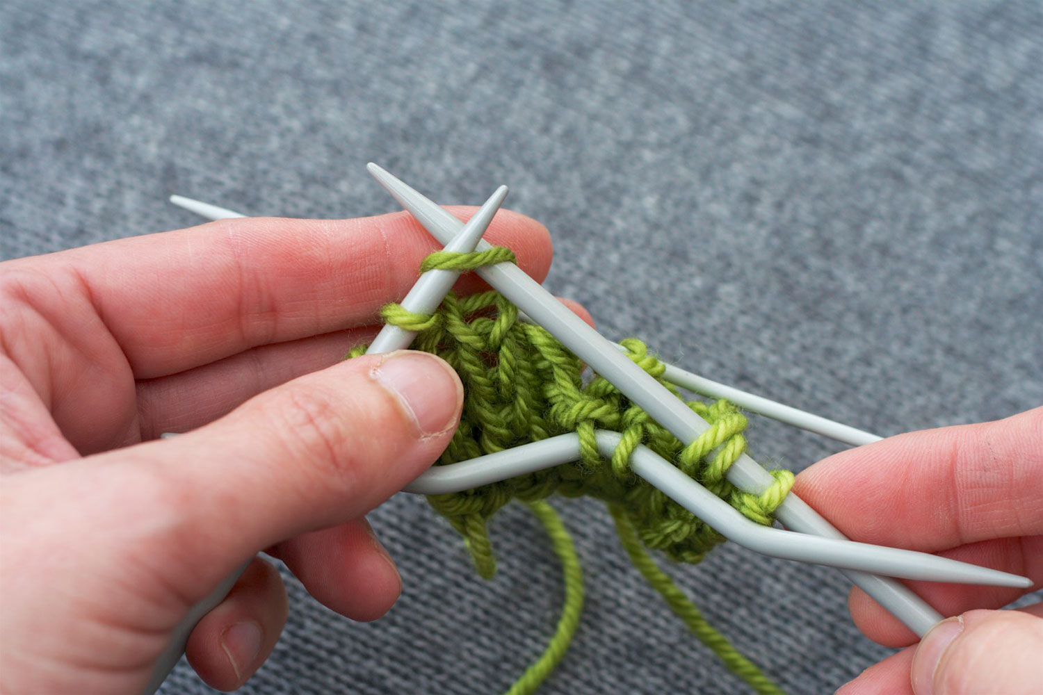 With one cable needle hanging at front and other at back, right needle is inserted in next stitch on left needle knitwise, preparing to knit the stitch.