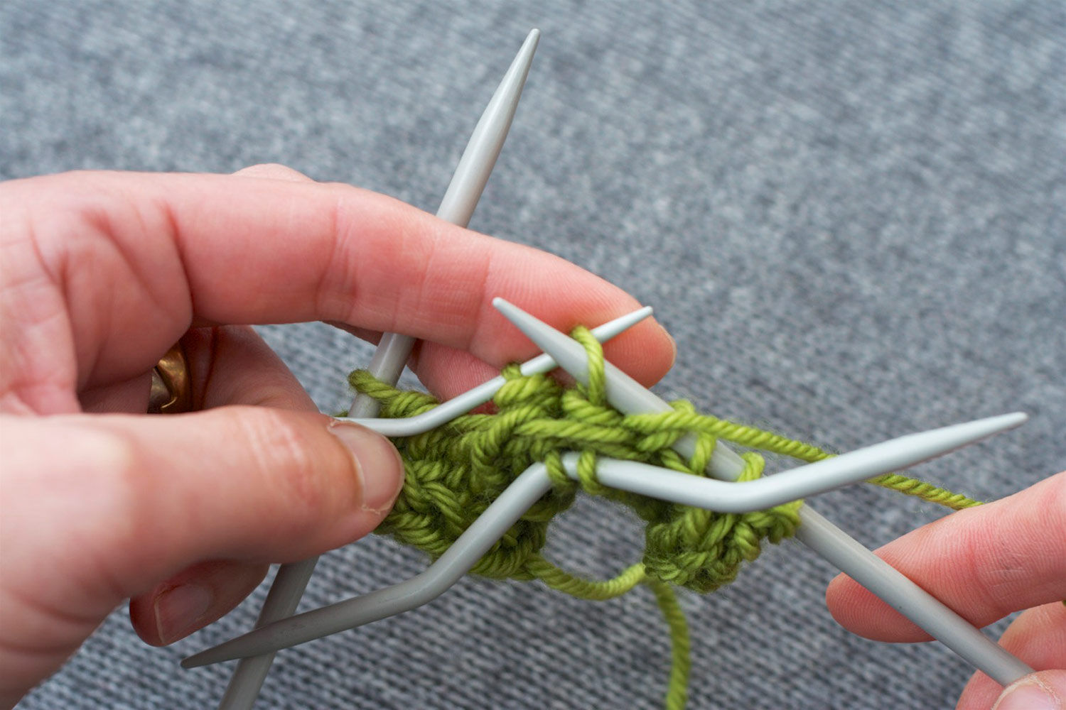 With cable needle hanging at front, right needle is inserted purlwise into next stitch on back cable needle, preparing to purl.