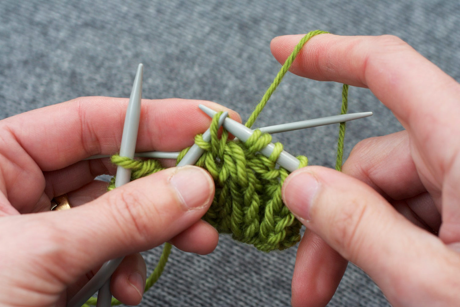 Right needle is inserted knitwise through the back of the loop into next stitch on front cable needle, preparing to knit it.