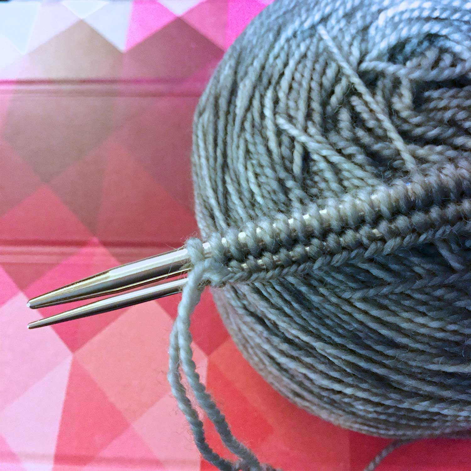 A cast on just worked on two needles (one larger, one smaller), sitting on top of a grey yarn cake, sitting on an iPad cover with red and pink triangles.