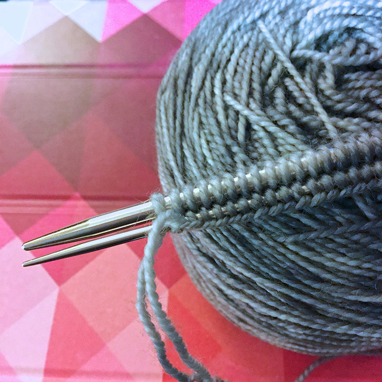 Stitches cast onto a larger needle with the lower edge of the cast on wrapped around a smaller needle.