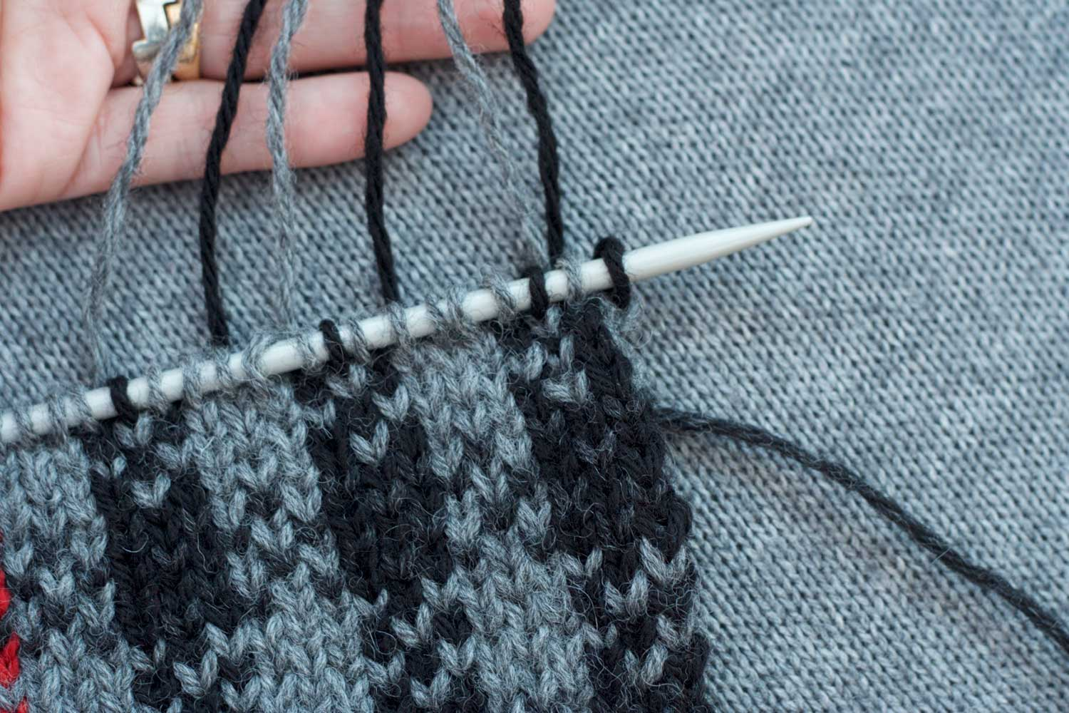 Grey and black plaid stitch pattern on the needles with several strands of yarn pulled up above the needle and laid across a hand.