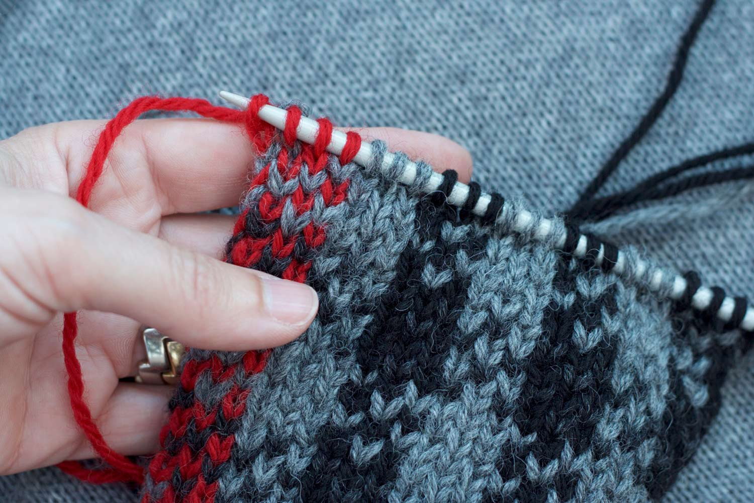 Hand holding knitting on the needles with right side facing showing a completed row of intarsia stitches; stitch pattern is black and grey plaid with one column of red stitches on left selvedge.