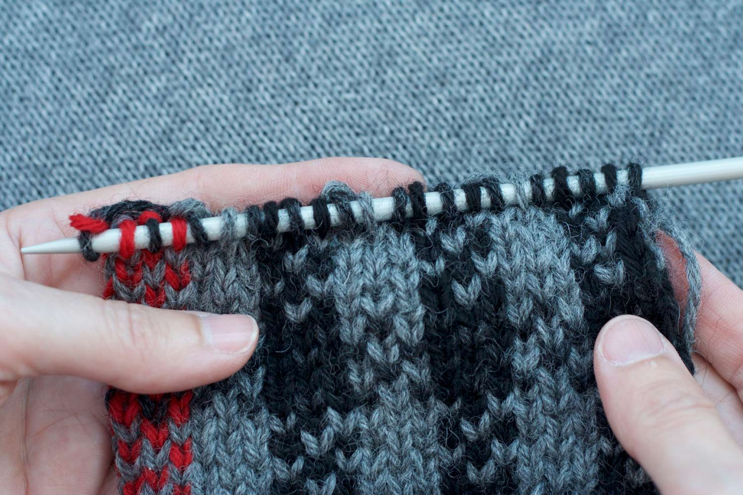 Hands hold knitting with right side facing showing a completed row of slipped stitches alternating with knit stitches.