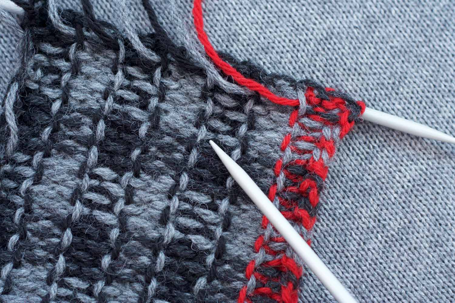 Knitting on the needle is laid on a knit background; wrong side is facing showing the intarsia joins running up the back side and the several strands of yarn needed for the intarsia columns.