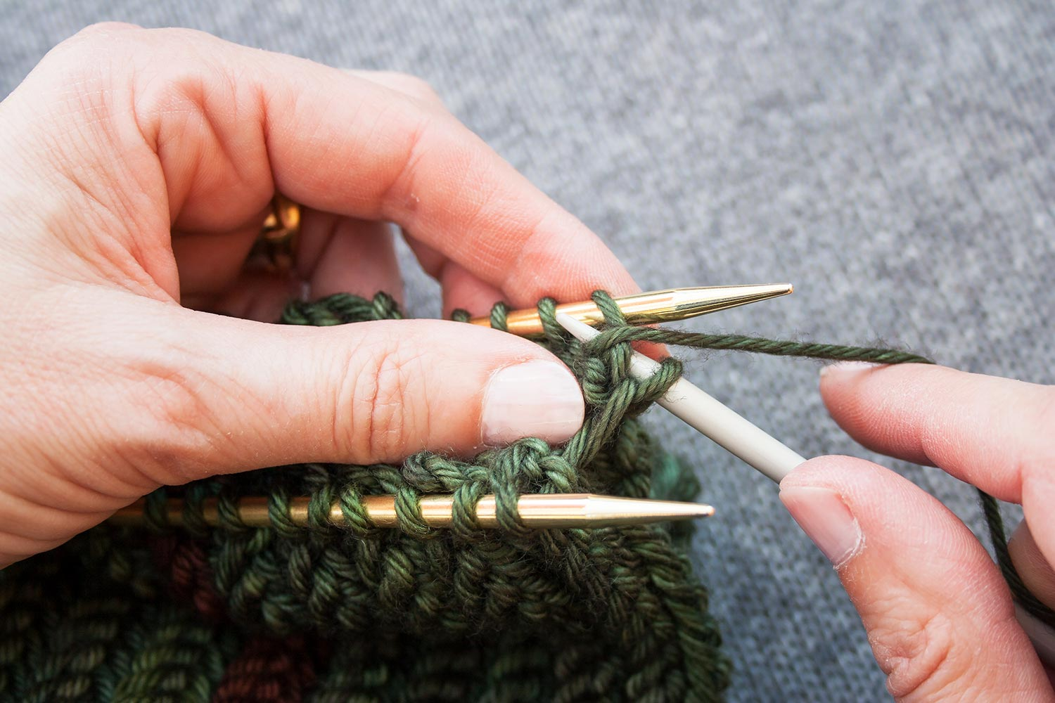 Third needle purling into first stitch on back needle.