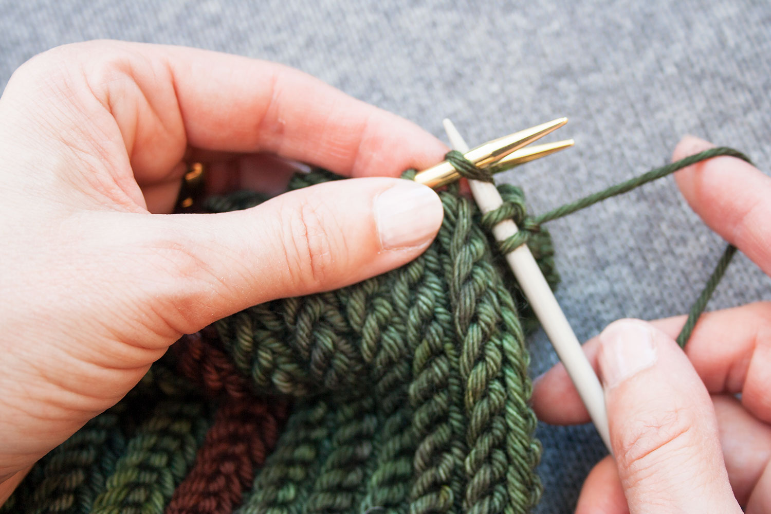 With two stitches already on third needle, it's inserted into the first stitch of the front needle knitwise.
