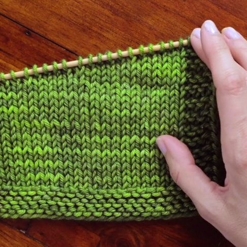 Short rows creating an angled final row on the needles.