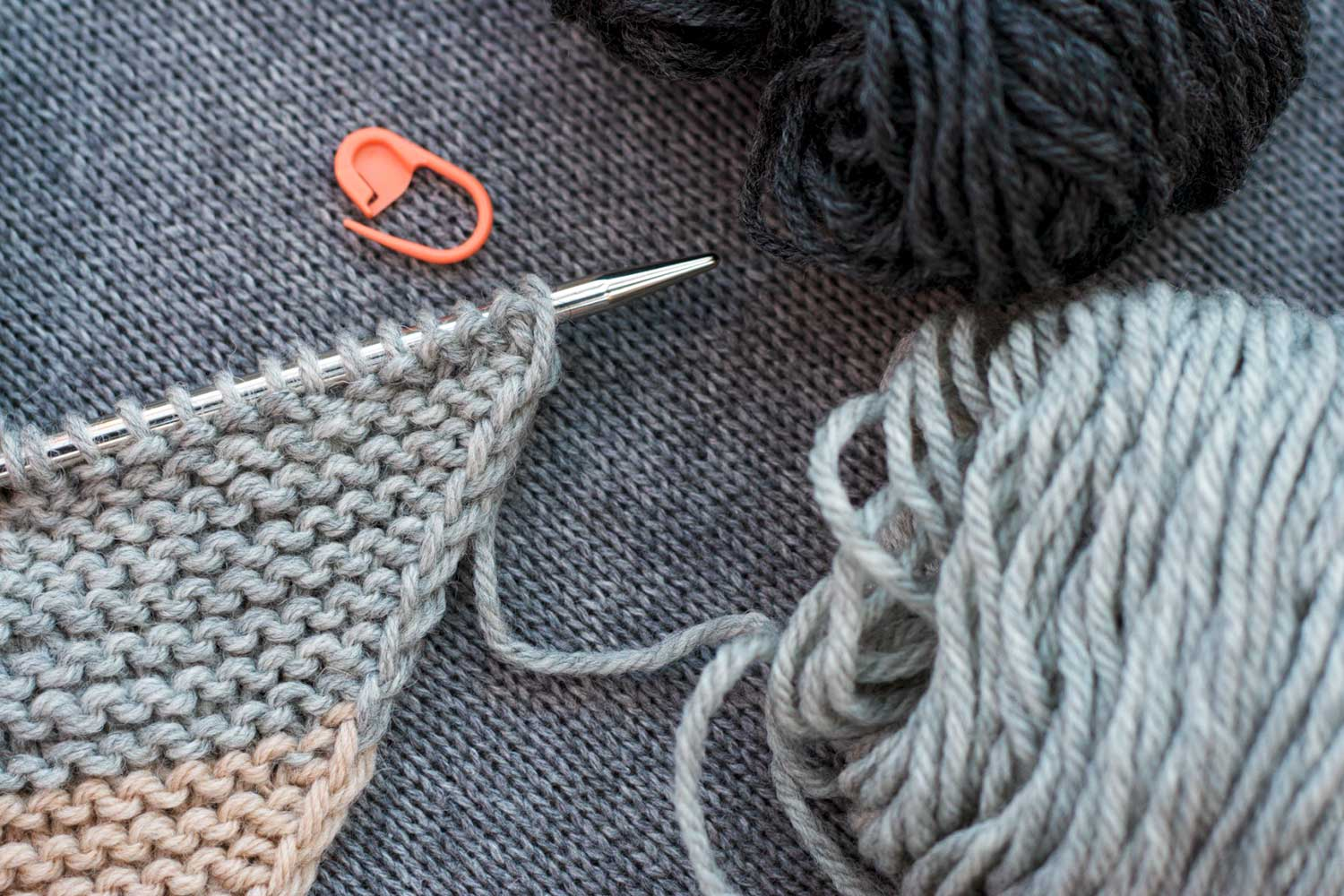 Supplies needed for spit splicing two colours includes knitting with yarn attached, a second colour of yarn, a locking stitch marker.