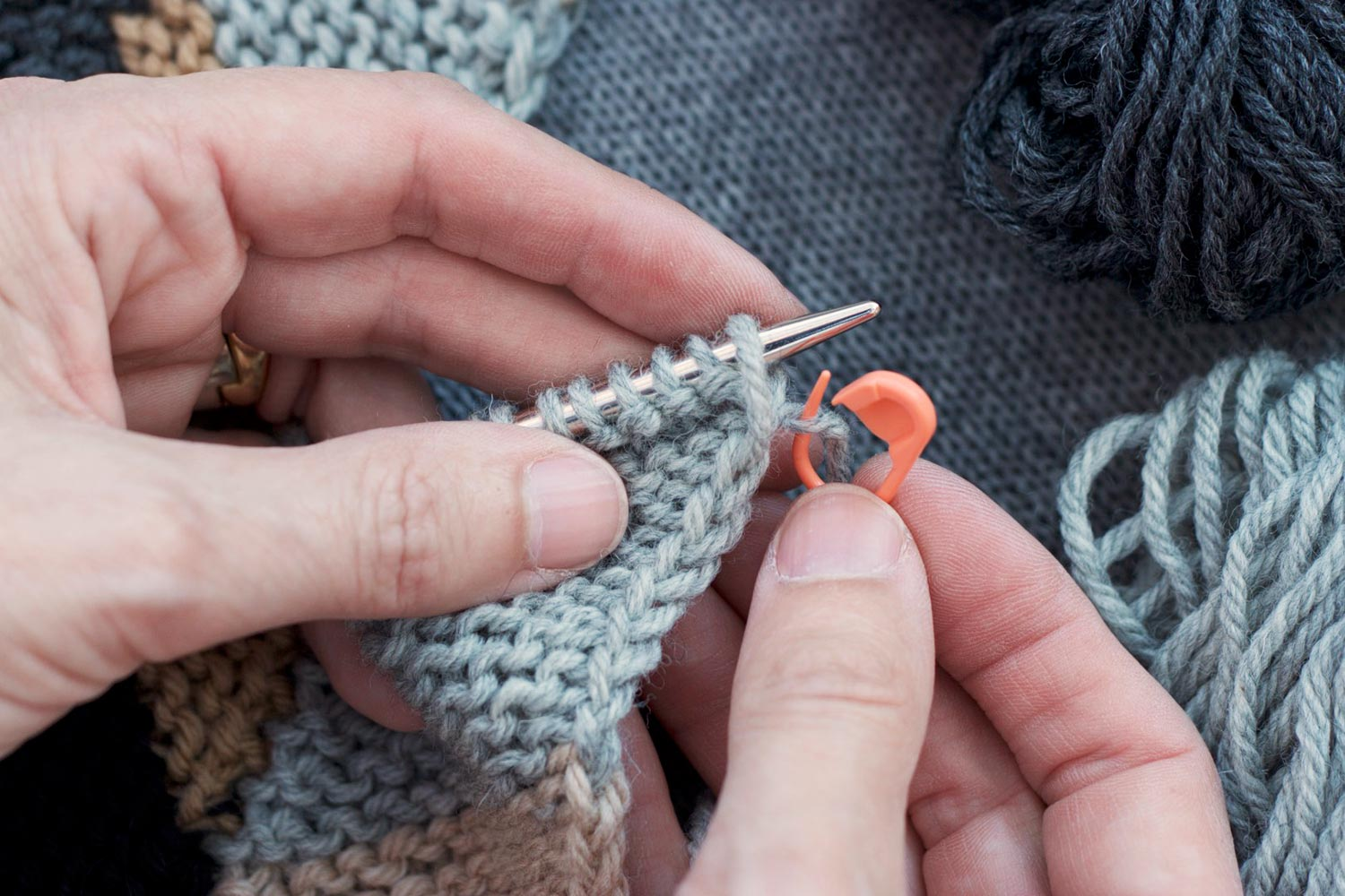 Left hand holding knitting on the needle and right hand holding a locking stitch marker that's piercing the working yarn next to the last stitch worked.