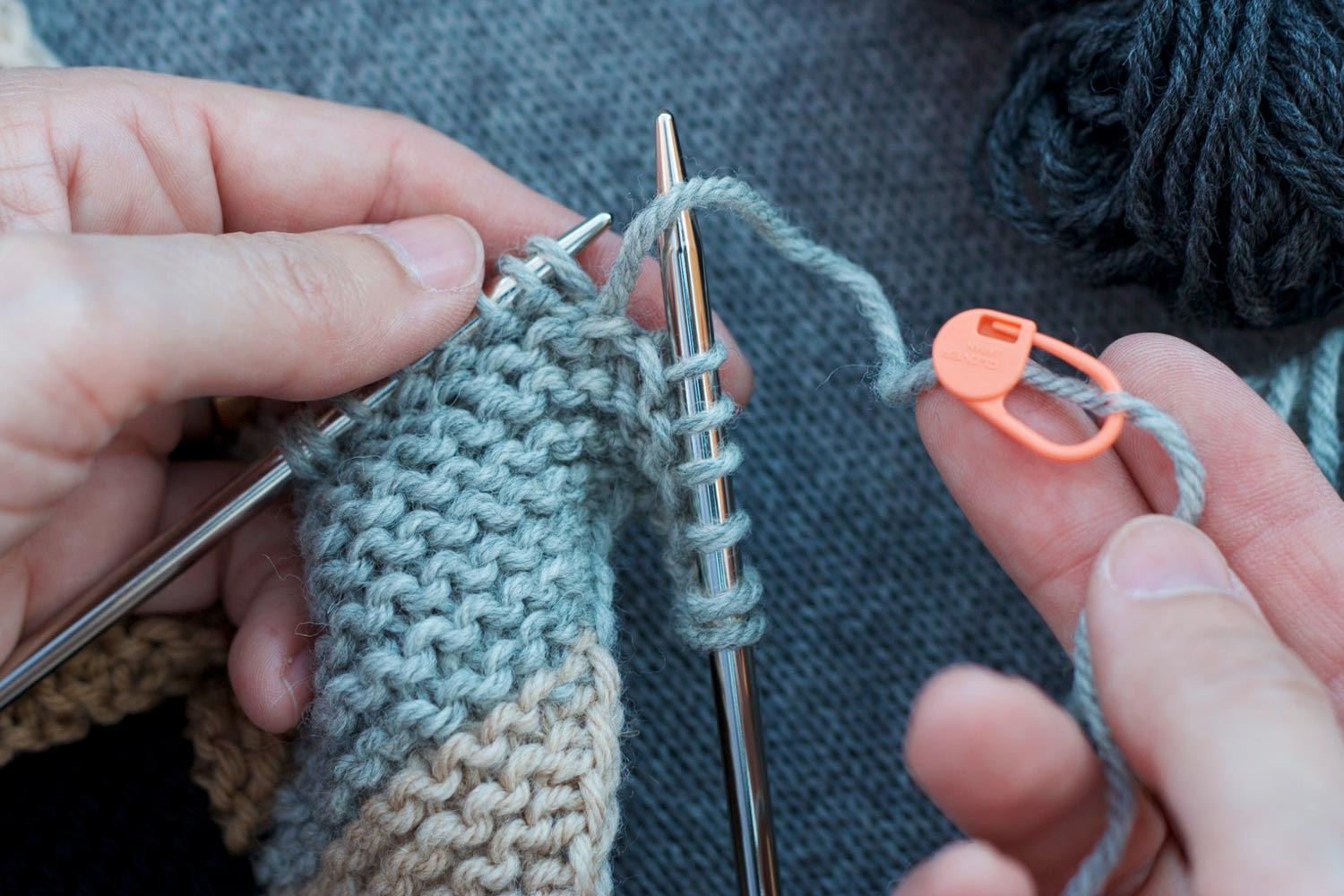 Six stitches unraveled on right needle and remaining stitches on left needle; right hand holds unraveled yarn with a stitch marker pinned several inches down its length.