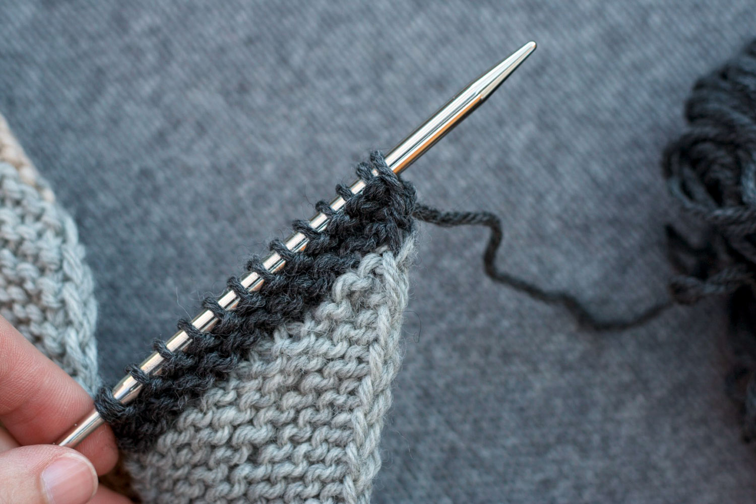 Several rows of light grey garter stitch with two charcoal grey ridges above, on the needles, showing that the two-colour join occurred perfectly at the end of a row.