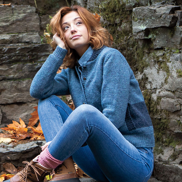 Woman sitting on rocks with legs crossed, wearing a cozy knitted bomber sweater.