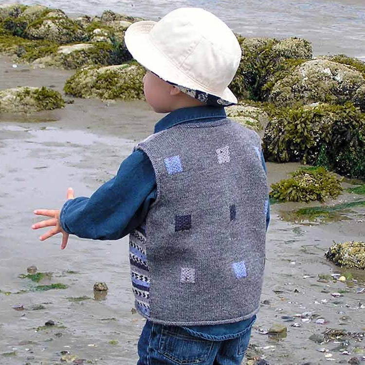 Small child at the beach wearing a vest with coloured squares on the back and self-patterning stripes on the front.