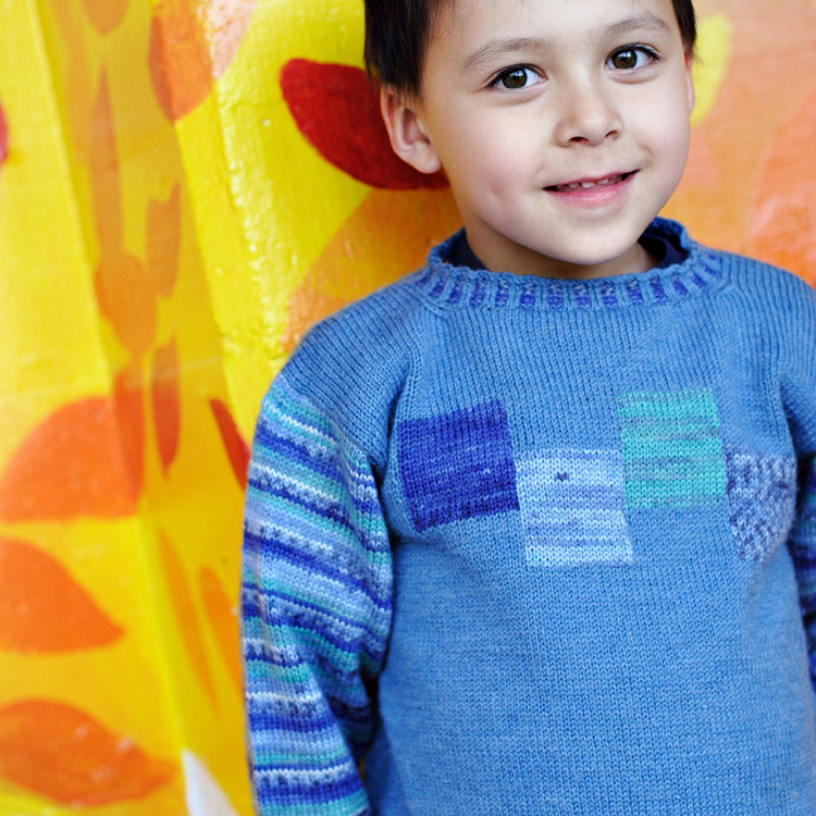 Child's pullover with intarsia blocks of colour on front and self-patterning striped sleeves.