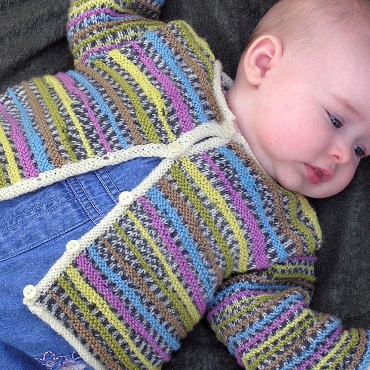 Baby lying on back wearing textured hand knit cardigan.